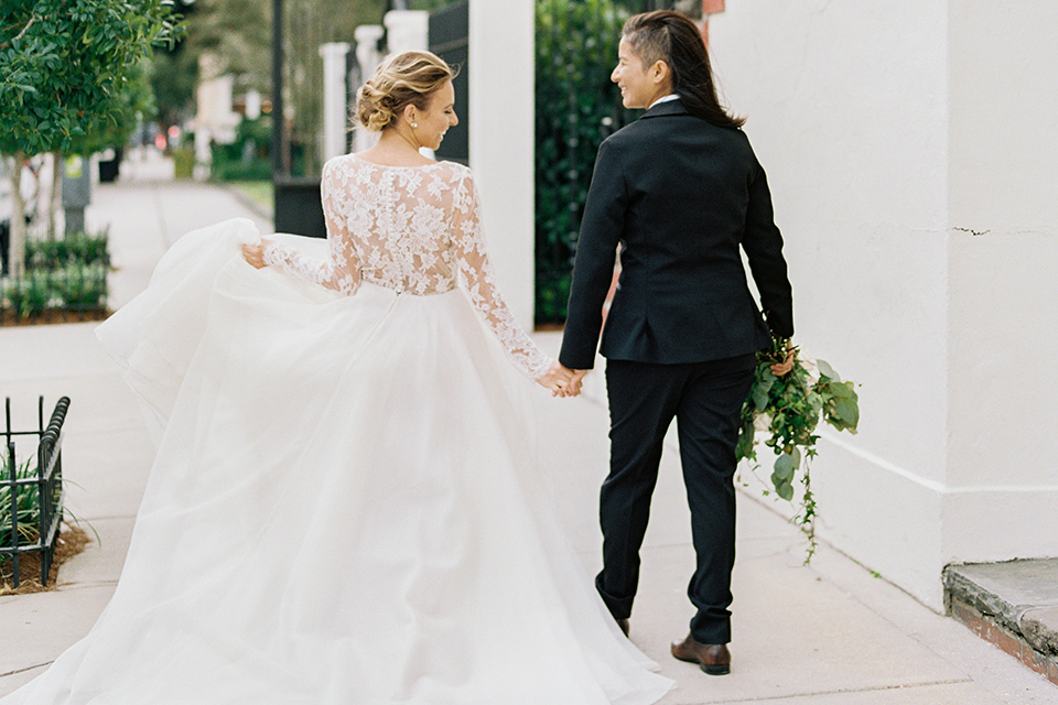 flower-market-shoot-brides-walking-away-from-camera-one-in-a-full-ball-gown-the-other-in-a-black-tuxedo