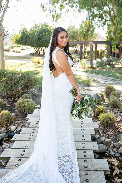 gallway-downs-wedding-bide-looking-at-camera-in-a-lace-formfitting-dress-with-a-high-neckline-and-keyhole-back