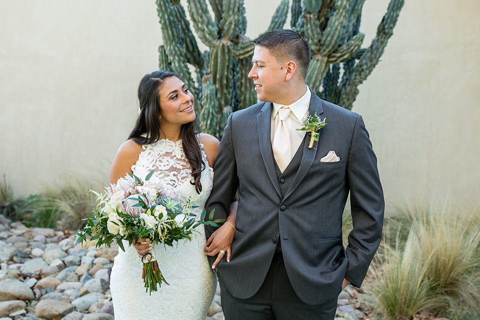 gallway-downs-wedding-bride-and-groom-by-cactus-smiling-at-each-other-bride-in-a-lace-form-fitting-gown-with-a-high-neckline-and-keyhole-back-groom-in-a-charcoal-tux-withan-ivory-long-tie