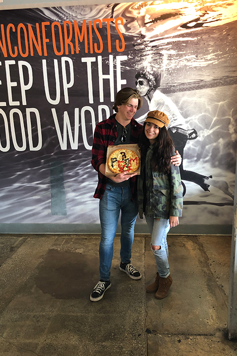 boy holding pizza spells prom at blaze pizza for his promposal