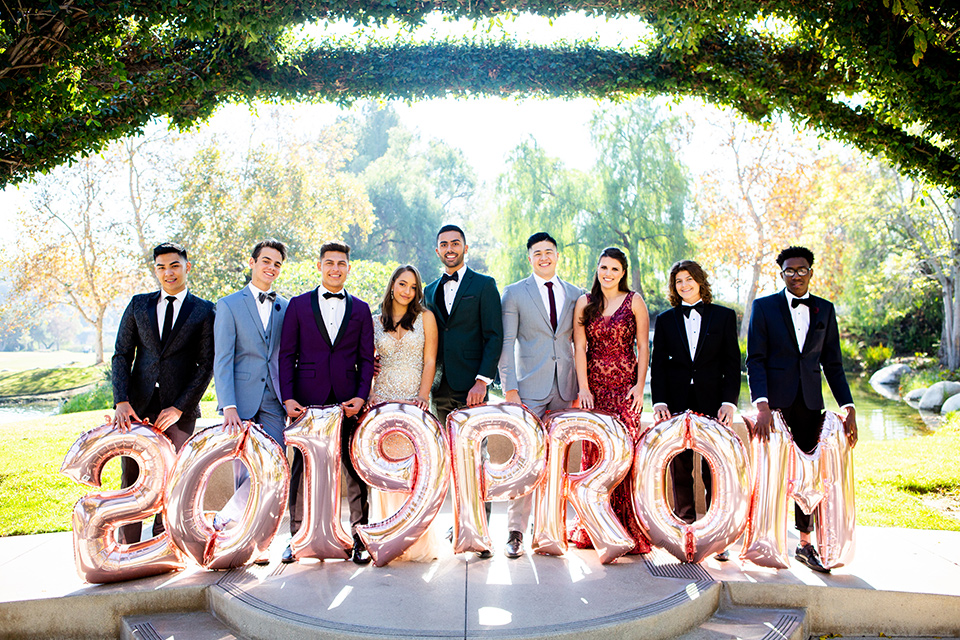 Group of friends pose for 2019 prom photo outdoors