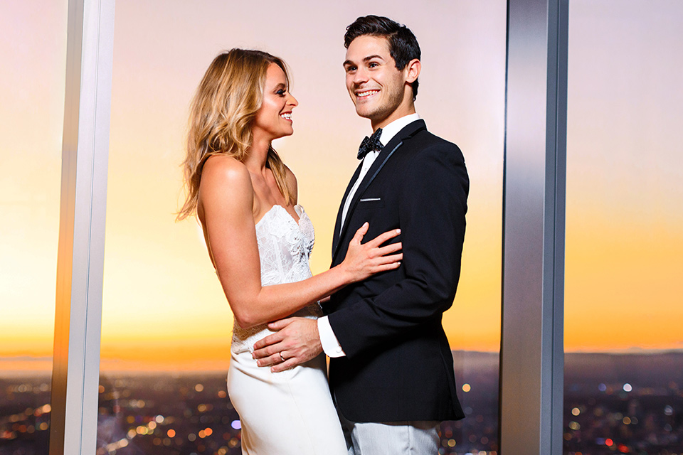 Intercontinental-DTLA-shoot-bride-and-groom-inside-with-sunset-behind-them-laughing-bride-wearing-a-stapless-white-gown-with-lace-detail-and-the-groom-wearing-a-two-toned-tuxedo-in-black-and-grey