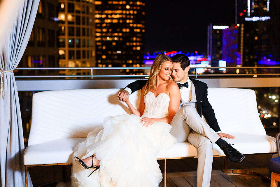 Intercontinental-DTLA-shoot-bride-and-groom-on-white-couch-bride-wearing-a-stapless-white-gown-with-lace-detail-and-the-groom-wearing-a-two-toned-tuxedo-in-black-and-grey