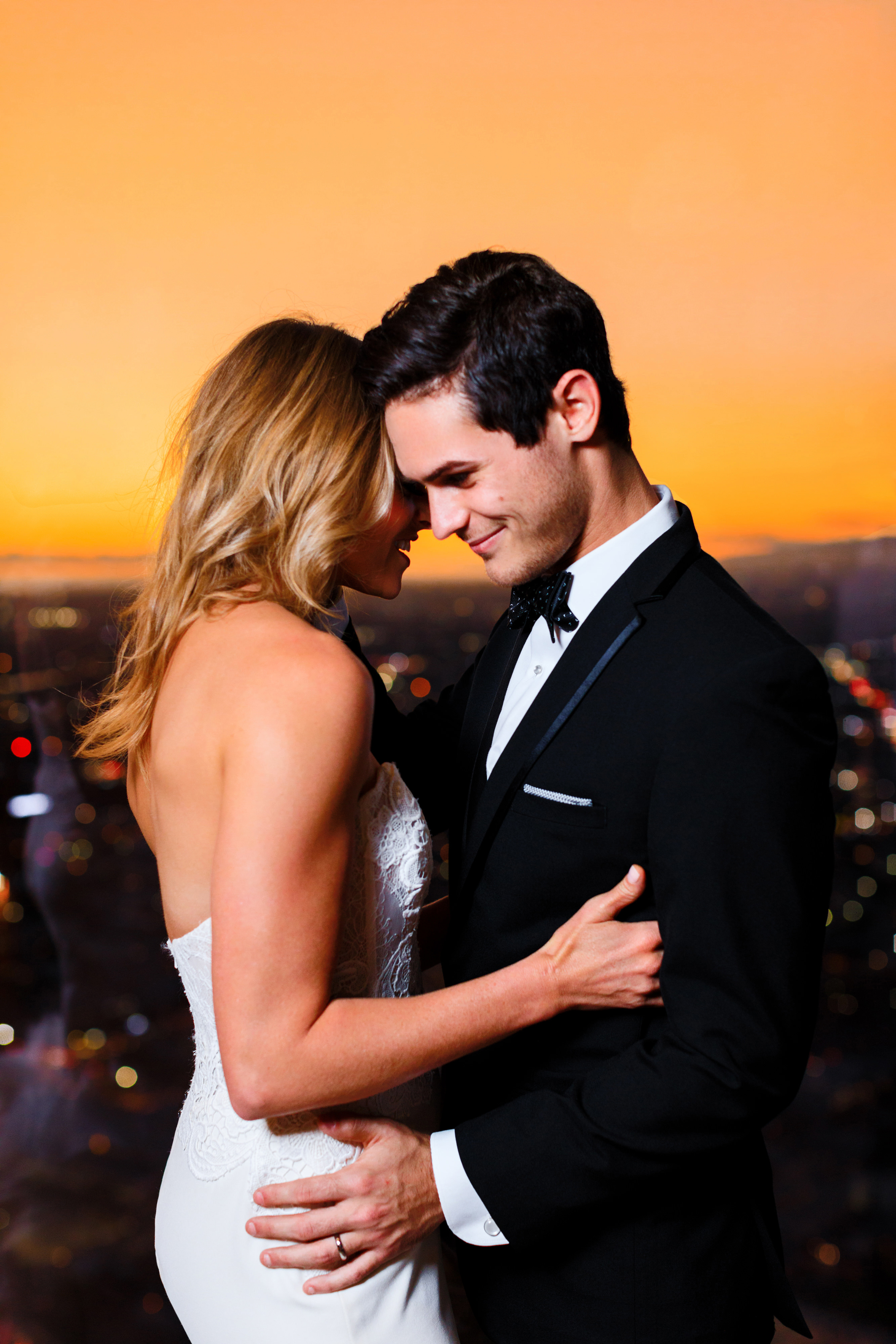 Intercontinental-DTLA-shoot-bride-and-groom-with-orange-sky-behind-them-bride-in-a-mermaid-gown-and-groom-in-a-black-tuxedo