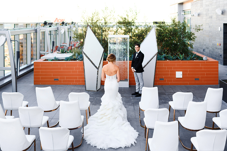 Intercontinental-DTLA-shoot-bride-walking-down-the-aisle-bride-wearing-a-stapless-white-gown-with-lace-detail-and-the-groom-wearing-a-two-toned-tuxedo-in-black-and-grey