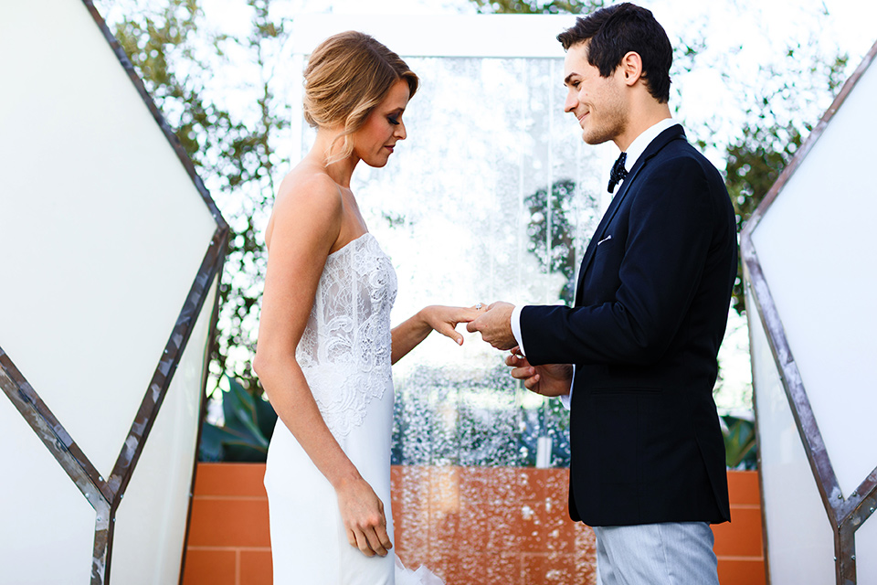 Intercontinental-DTLA-shoot-exchanging-rings-bride-wearing-a-stapless-white-gown-with-lace-detail-and-the-groom-wearing-a-two-toned-tuxedo-in-black-and-grey