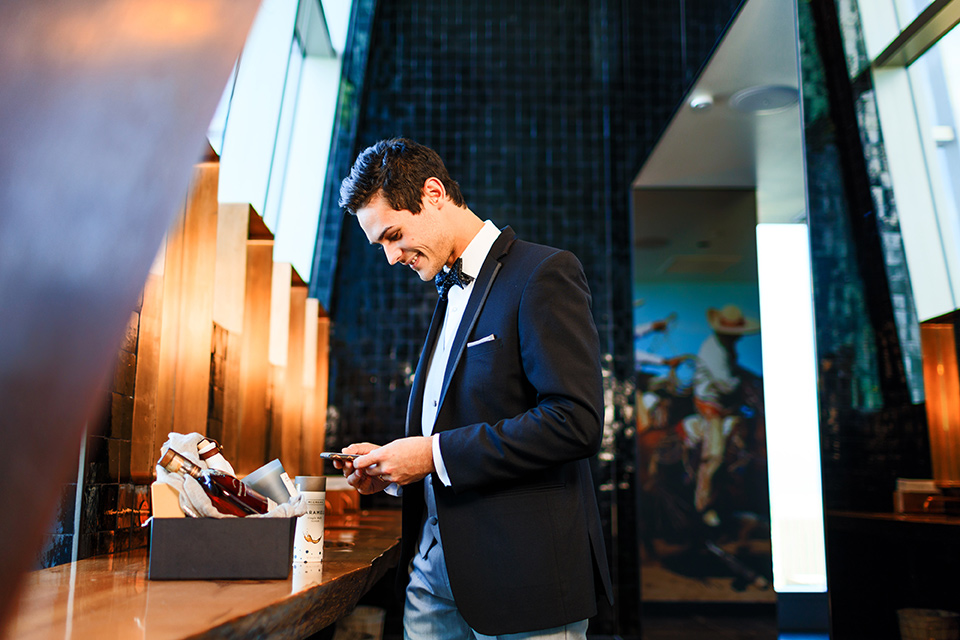 Intercontinental-DTLA-shoot-groom-looking-at-gift-basket-groom-wearing-a-two-toned-tuxedo-in-black-and-grey