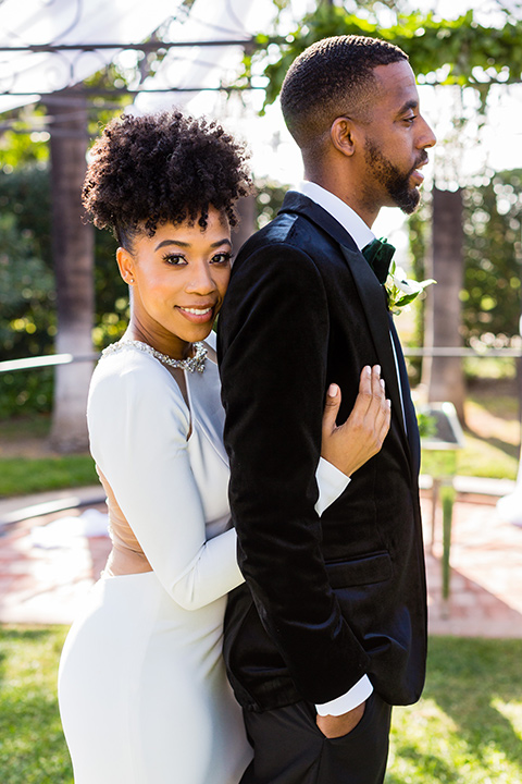 muckenthaler-mansion-bride-and-groom-close-up-bride-looking-at-camera-in-a-satin-gown-with-an-illusion-back-and-groom-in-a-black-velet-tux