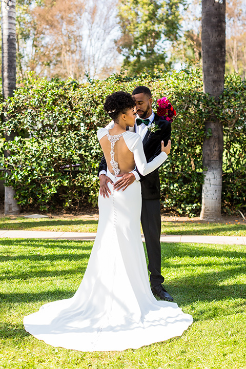 muckenthaler-mansion-bride-and-groom-dancing-in-a-satin-white-gown-and-long-sleeves-and-groom-in-a-black-velvet-tuxedo-and-green-velvet-bow-tie