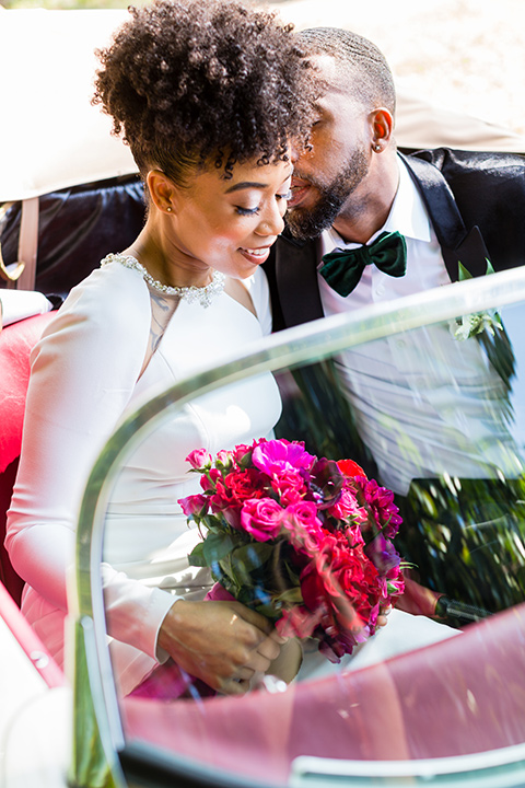 muckenthaler-mansion-bride-and-groom-driving-in-car-bride-looking-at-camera-in-a-satin-gown-with-an-illusion-back-and-groom-in-a-black-velet-tux