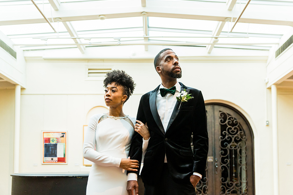 muckenthaler-mansion-bride-and-groom-looking-away-from-each-other-bride-in-a-vintage-satin-gown-and-groom-in-a-velvet-tuxedo-with-a-green-velvet-bow-tie