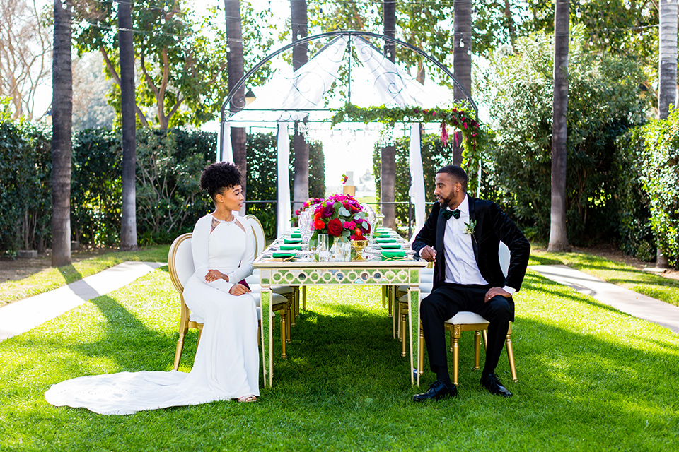 muckenthaler-mansion-bride-groom-at-table-bride-in-a-vintage-satin-gown-and-groom-in-a-velvet-tuxedo-with-a-green-velvet-bow-tie