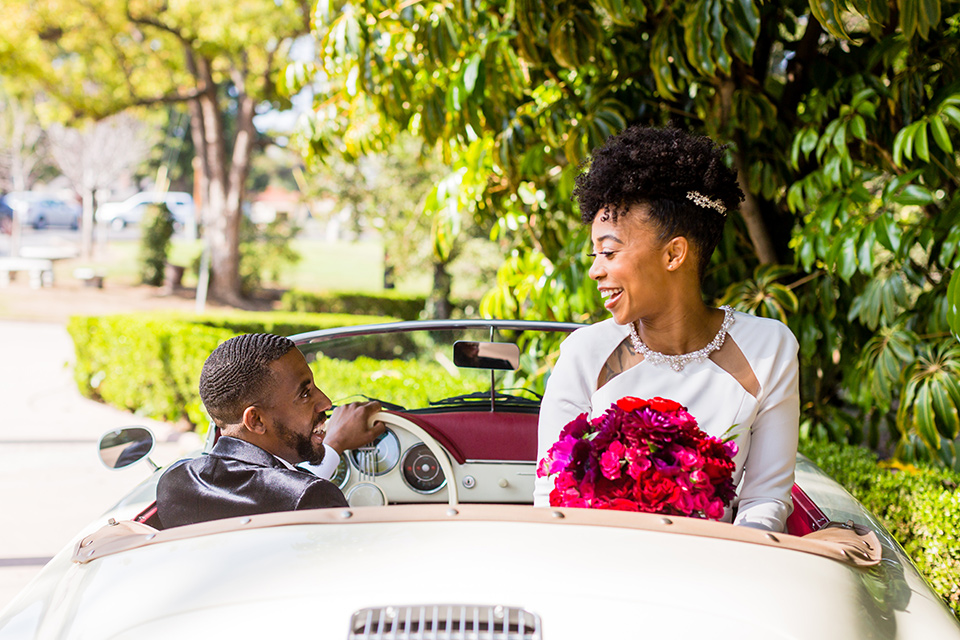 muckenthaler-mansion-couple-driving-away-bride-in-a-vintage-satin-gown-and-groom-in-a-velvet-tuxedo-with-a-green-velvet-bow-tie