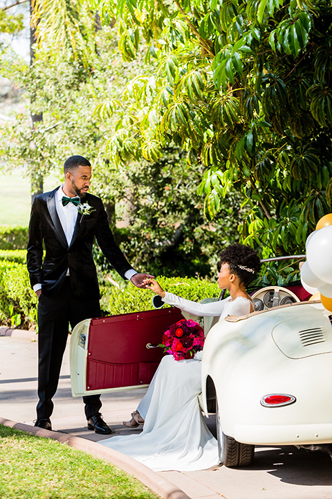 muckenthaler-mansion-groom-helping-bride-out-of-car-bride-in-a-satin-white-gown-and-long-sleeves-and-groom-in-a-black-velvet-tuxedo-and-green-velvet-bow-tie