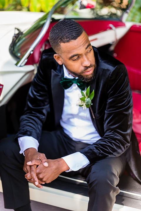 muckenthaler-mansion-groom-sitting-in-car-groom-in-a-black-velvet-tuxedo-and-green-velvet-bow-tie