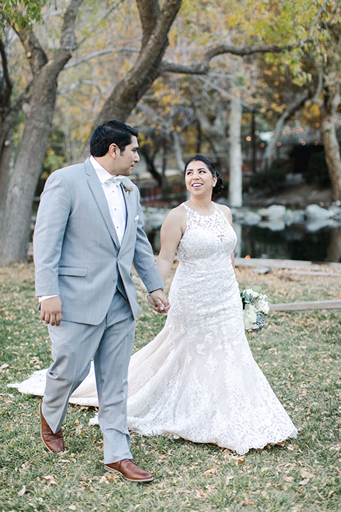 hidden-acres-wedding-bride-and-groom-walking-bride-in-a-fitted-lace-gown-with-groom-in-grey-suit-with-white-bow-tie