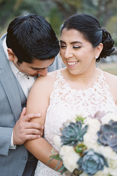 hidden-acres-wedding-close-up-of-ciuple-groom-kissing-her-shoulder-bride-in-fitted-gown-with-lace-detailing-groom-in-light-grey-suit