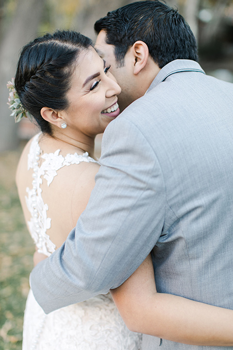 hidden-acres-wedding-close-up-on-bride-and-groom-bride-in-a-fitted-lace-gown-with-groom-in-grey-suit-with-white-bow-tie
