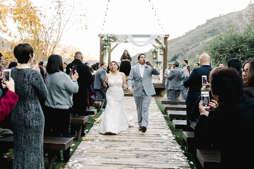 hidden-acres-wedding-drinking-beers-as-they-end-ceremony-bride-in-fitted-gown-with-an-illusion-neckline-and-groom-in-a-grey-suit-with-a-white-bow-tie