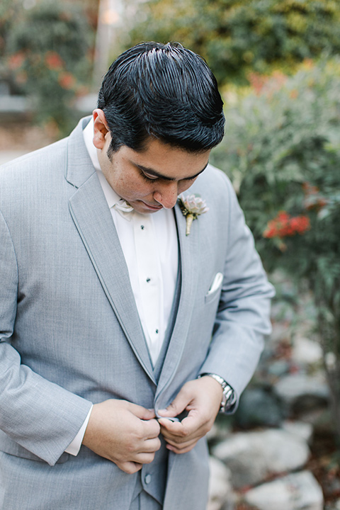 hidden-acres-wedding-groom-buttoning-jacket-groom-in-grey-suit-with-white-bow-tie