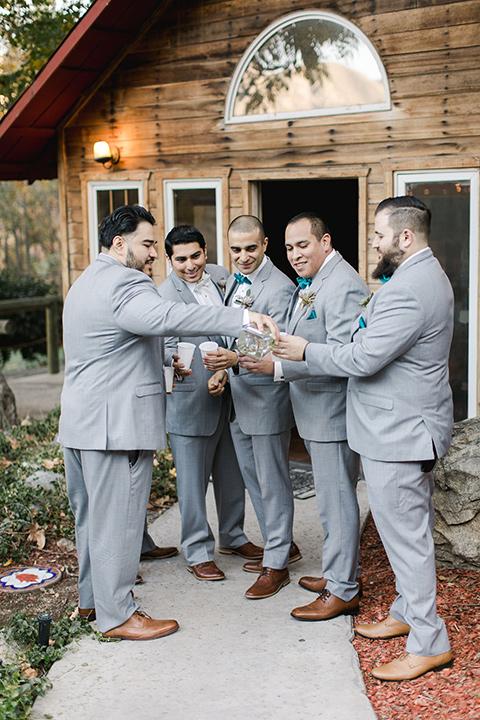 hidden-acres-wedding-groomsmen-cheersing-all-in-light-grey-suits