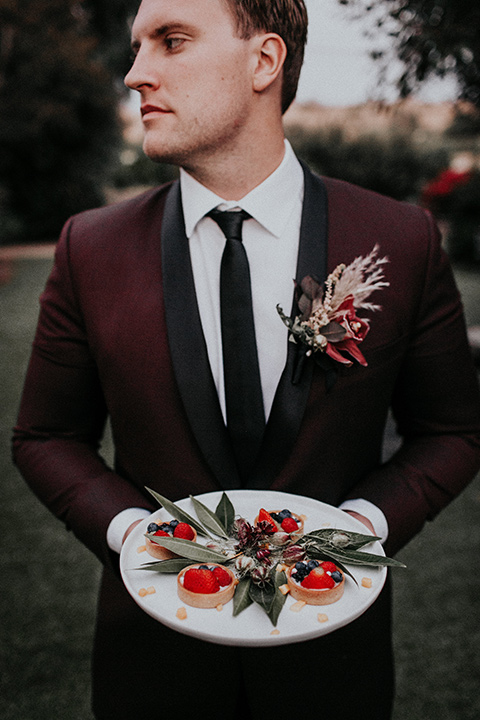 orange-county-vow-groom-holding-the-plate-groom-in-a-burgundy-tuxedo-with-a-black-shawl-lapel