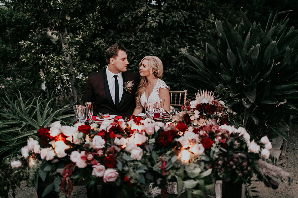 orange-county-vow-renewal-bride-and-groom-at-sweetheart-table-bride-in-a-lace-modern-fitted-gown-with-a-nude-underlay-groom-in-a-burgundy-tuxedo-with-a-black-shawl-lapel