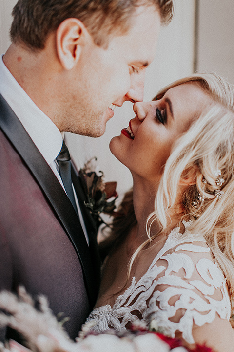 orange-county-vow-renewal-bride-and-groom-close-up-bride-in-a-lace-modern-fitted-gown-with-a-nude-underlay-groom-in-a-burgundy-tuxedo-with-a-black-shawl-lapel