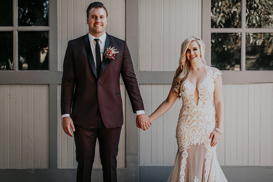 orange-county-vow-renewal-bride-and-groom-smiling-looking-at-camera-bride-in-a-lace-modern-fitted-gown-with-a-nude-underlay-groom-in-a-burgundy-tuxedo-with-a-black-shawl-lapel