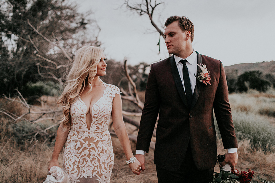 orange-county-vow-renewal-brode-and-groom-walking-and-looking-at-each-other-bride-in-a-lace-modern-fitted-gown-with-a-nude-underlay-groom-in-a-burgundy-tuxedo-with-a-black-shawl-lapel