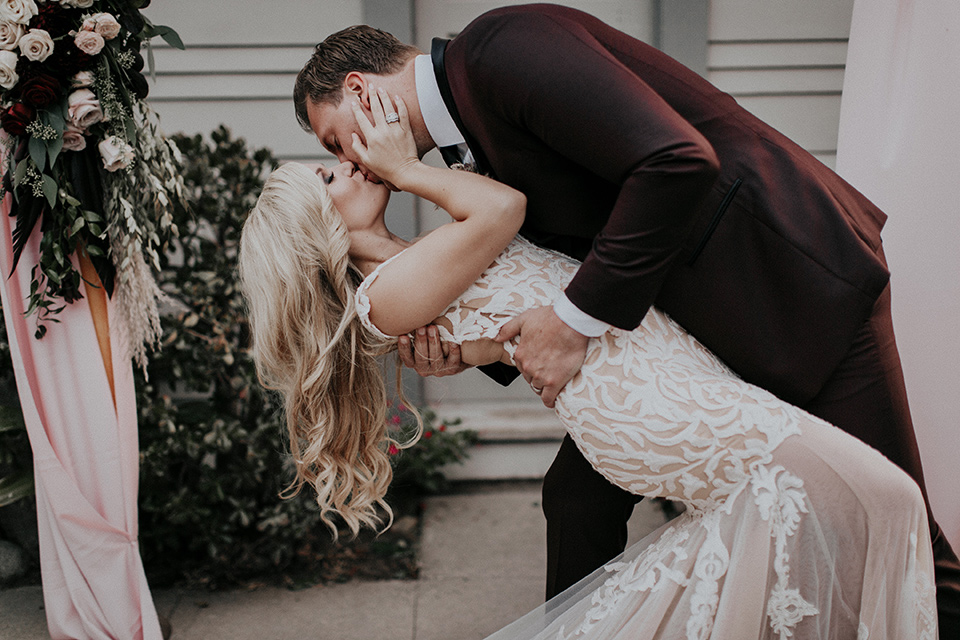 orange-county-vow-renewal-first-kiss-bride-in-a-lace-modern-fitted-gown-with-a-nude-underlay-groom-in-a-burgundy-tuxedo-with-a-black-shawl-lapel