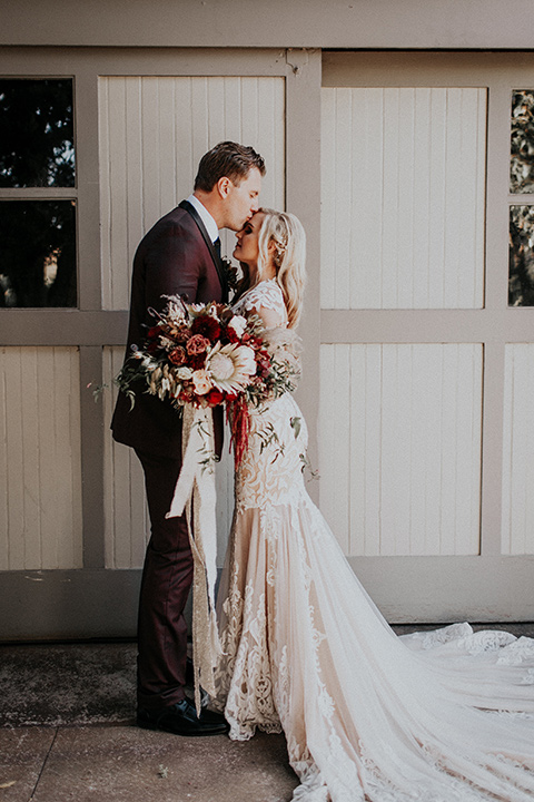 orange-county-vow-renewal-groom-kissing-bride-on-forehead-bride-in-a-lace-modern-fitted-gown-with-a-nude-underlay-groom-in-a-burgundy-tuxedo-with-a-black-shawl-lapel