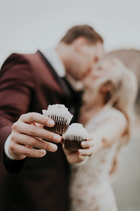 orange-county-vow-renewal-holding-cupcakes-bride-in-a-lace-modern-fitted-gown-with-a-nude-underlay-groom-in-a-burgundy-tuxedo-with-a-black-shawl-lapel