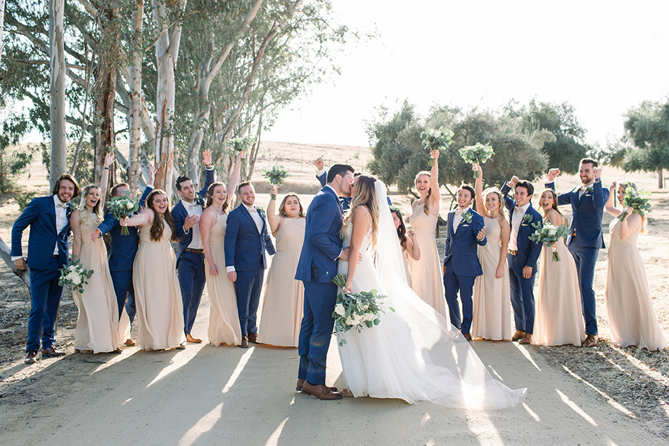 bride in a white a line gown with straps and a big white and sage floral bouquet and cathedral length veil, the groom in a dark blue suit with a white bow tie, the groomsmen in blue suits and champagne ties and the bridesmaids in neutral long gowns