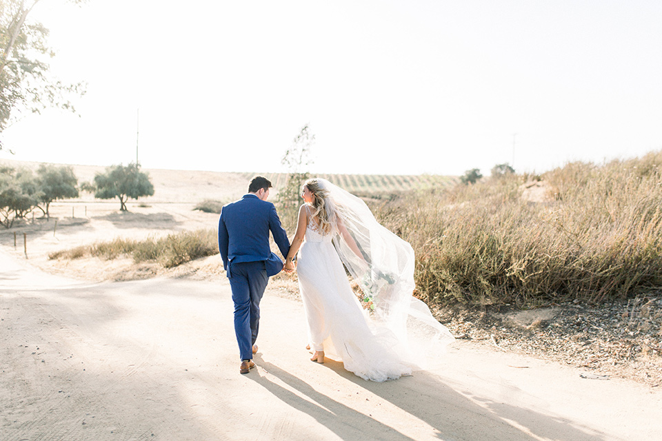 bride in a white a line gown with straps and a big white and sage floral bouquet and cathedral length veil, the groom in a dark blue suit with a white bow tie