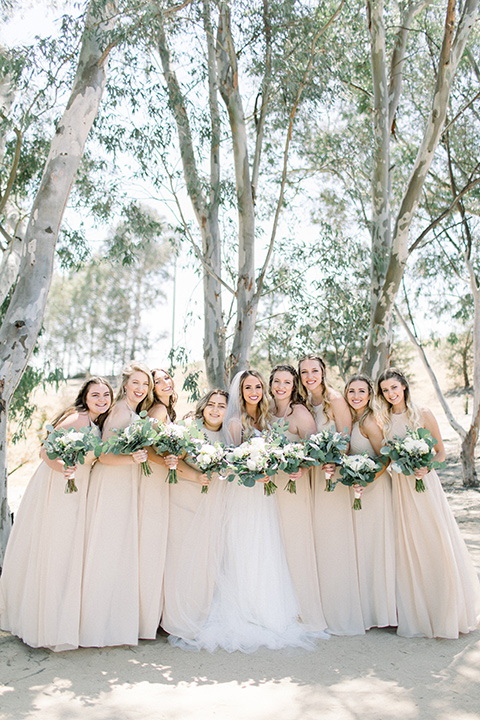 bride in a white a line gown with straps and a big white and sage floral bouquet and cathedral length veil, bridesmaids in neutral long gowns