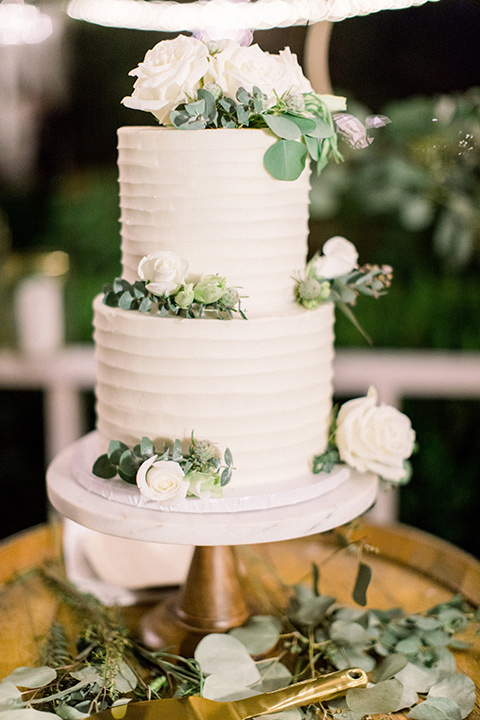 white three tiered cake with green accents