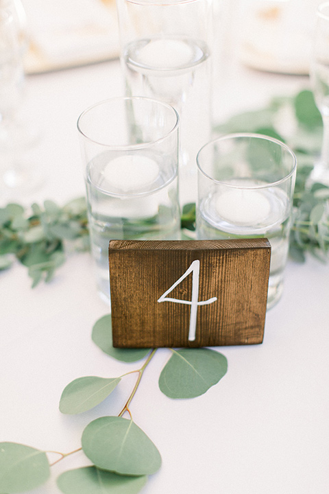 white linens with sage and wooden number cards