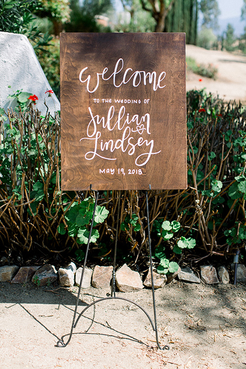 wooden sign with the bride and groom welcoming guests