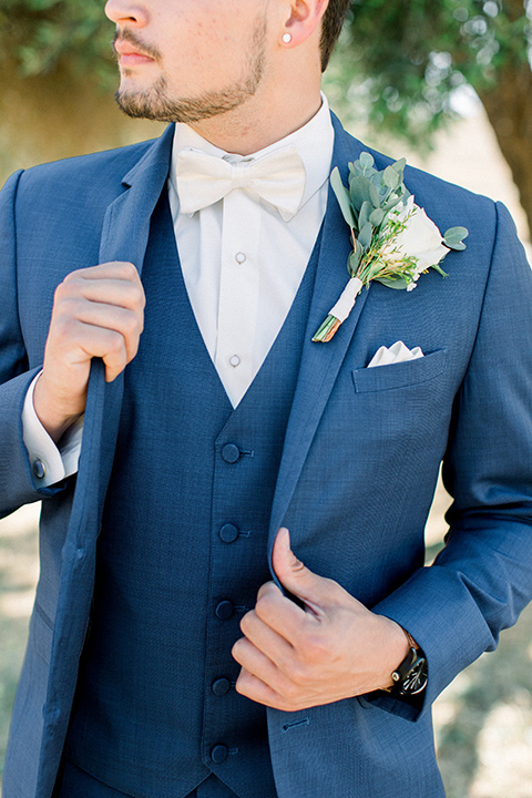 the groom in a dark blue suit with a white bow tie