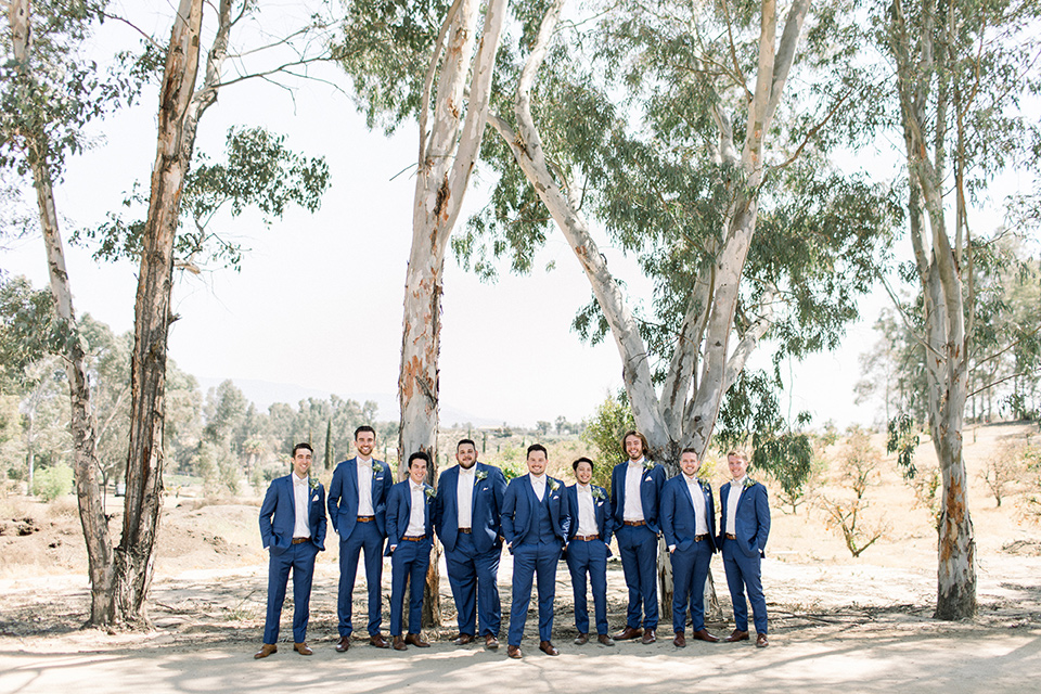the groom and groomsmen in a dark blue suits with a white bow ties