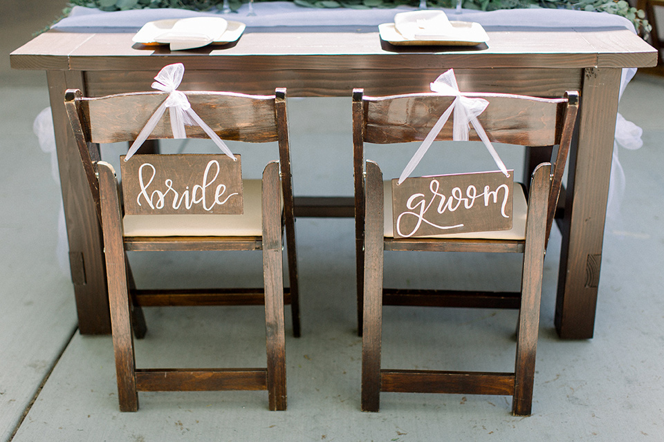 wooden table with wooden signs with bride and groom written on them