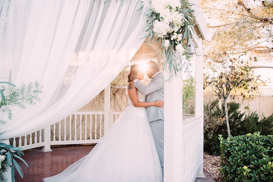 little-chapel-on-the-corner-las-vegas-wedding-shoot-bride-and-groom-in-gazeebo-while-the-bride-wore-a-tulle-ballgown-with-skinny-straps-and-the-groom-wore-a-heather-grey-suit
