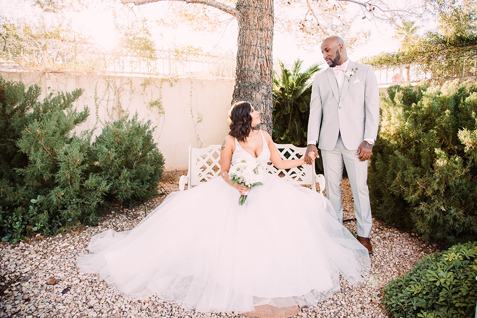 little-chapel-on-the-corner-las-vegas-wedding-shoot-bride-sitting-groom-standing-the-bride-wore-a-tulle-ballgown-with-skinny-straps-and-the-groom-wore-a-heather-grey-suit