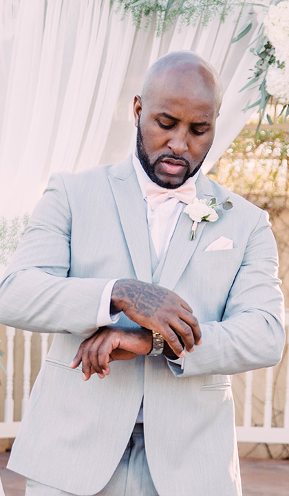 little-chapel-on-the-corner-las-vegas-wedding-shoot-groom-adjusting-watch-while-wearing-a-light-grey-suit-and-ink-bow-tie