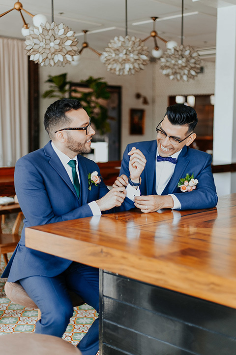 loquita-shoot-close-up-of-grooms-at-bar-grooms-in-cobalt-blue-suits-with-a-green-tie-and-a-blue-bow-tie