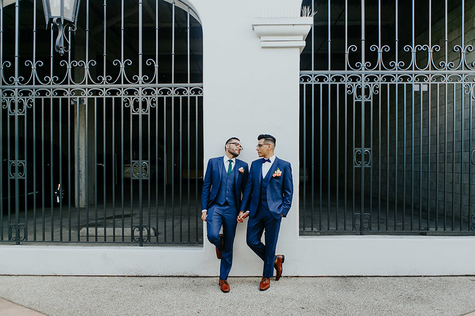 loquita-shoot-grooms-against-wall-looking-at-each-other-grooms-in-cobalt-blue-suits-with-one-with-a-green-tie-and-the-other-with-a-blue-bow