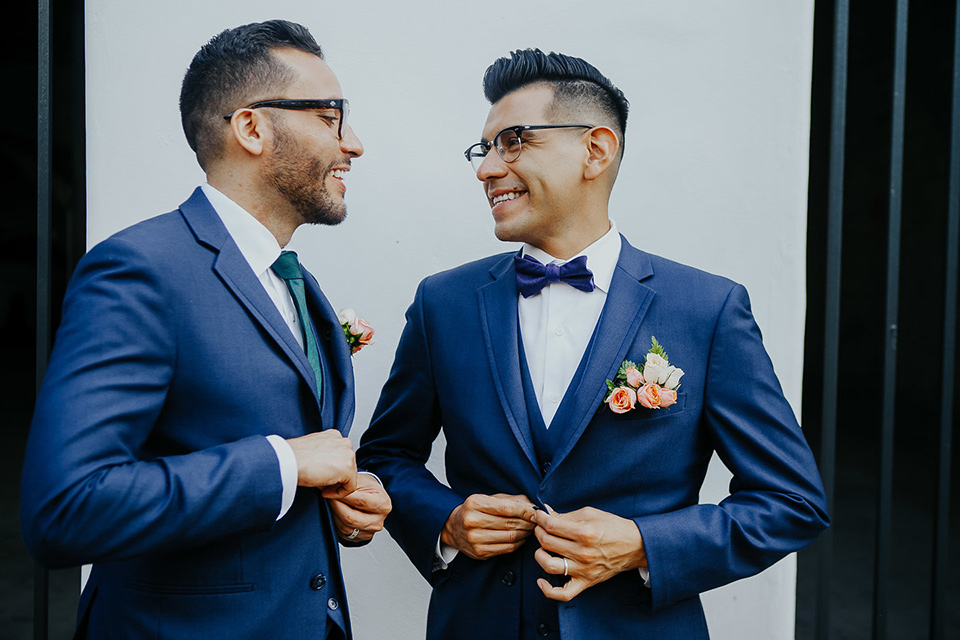 loquita-shoot-grooms-laughing-looking-at-each-other-grooms-in-cobalt-blue-suits-with-one-with-a-green-tie-and-the-other-with-a-blue-bow