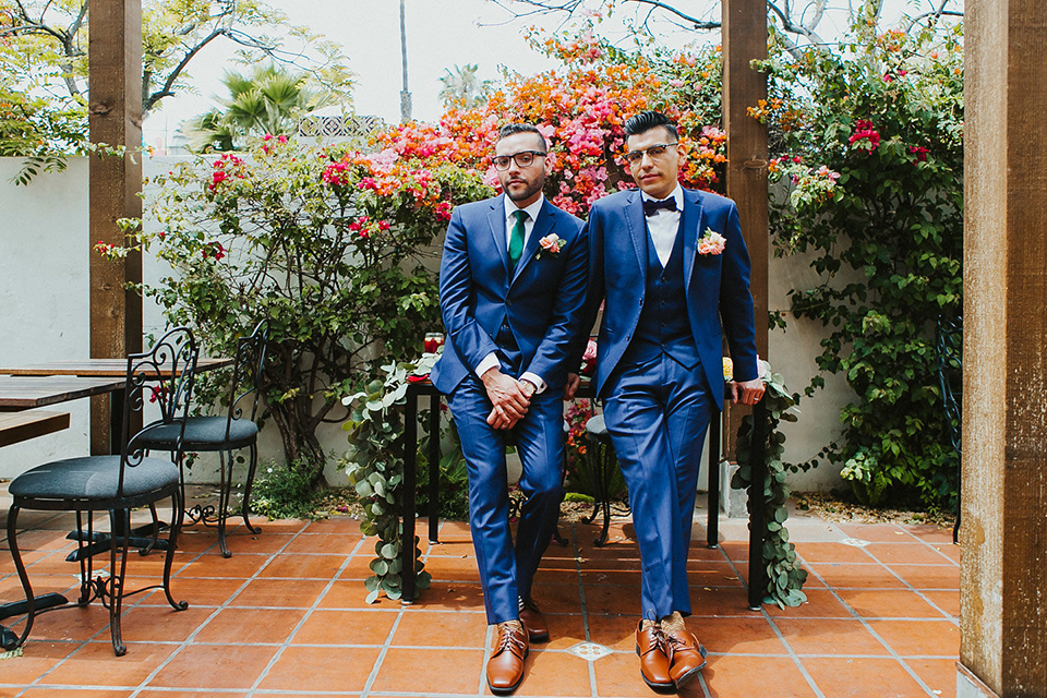 loquita-shoot-grooms-outside-sitting-on-table-grooms-in-cobalt-blue-suits-with-one-with-a-green-tie-and-the-other-with-a-blue-bow