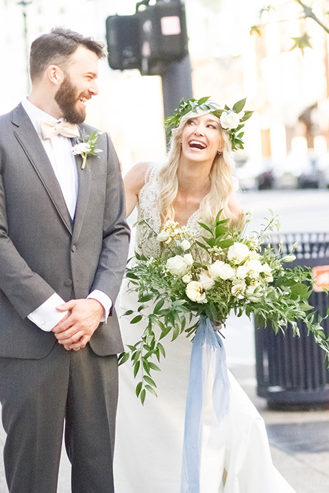 luce-loft-bride-and-groom-laughing-outside-bride-in-a-fit-and-flare-gown-with-straps-groom-in-a-charcoal-suit-with-champagne-bow-tie